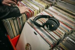 Kopfhörer: Bild von vielen Schallplatten, auf welchen ein Kopfhörer liegt